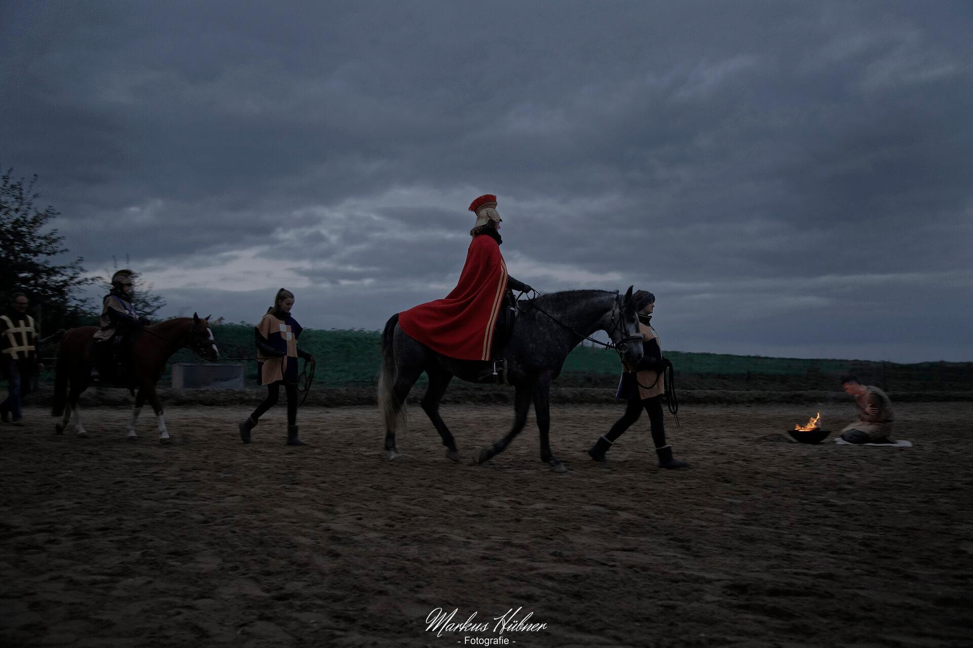 Sankt Martin reitet zum am Feuer kauernden Bettler